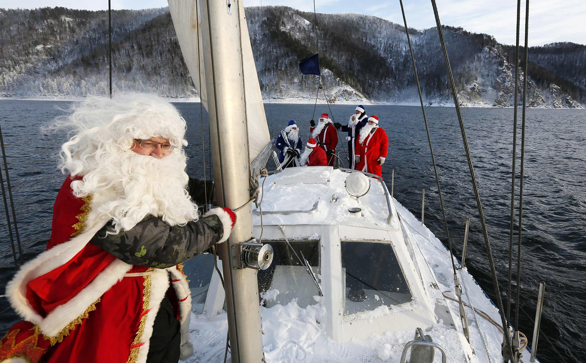 "Members of the ""Skipper"" yacht club dressed as Father Frost, Russian equivalent of Santa Claus sail a yacht to mark the end of the sailboat season on the Yenisei River, outside Krasnoyarsk"