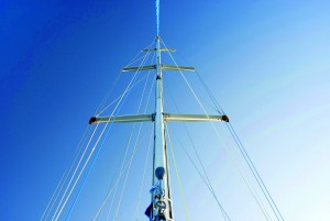 Low angle view of the mast and rigging of a small pleasure yacht against a clear blue sky